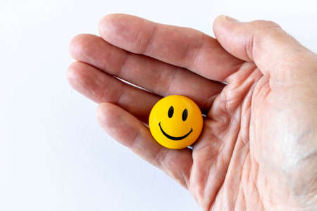 Funny plastic smiley face in a human hand. The concept of a positive mood