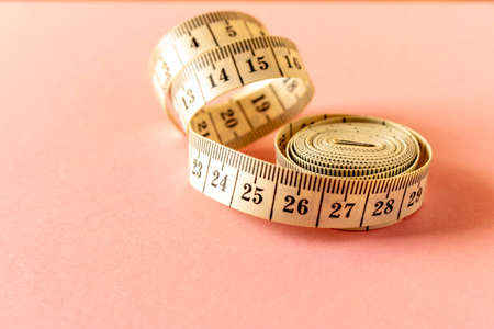White measuring tape on a pink background. Close-up