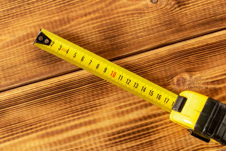 Yellow measuring tape on a wooden background. Close-up