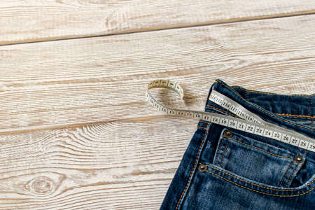 Measuring tape for weight loss in jeans on a wooden background. The concept of being overweight. Selective focus