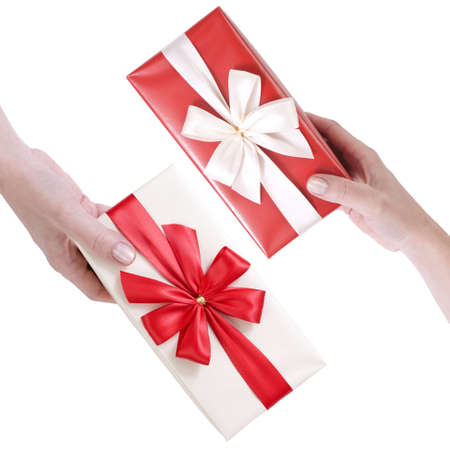 female hand holding red and white gift boxes with a bow isolated on white background  photo