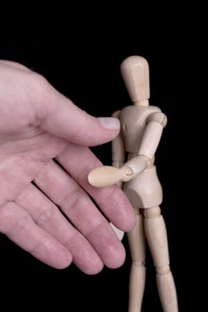manequin: Wooden dummie shaking human hand over black background