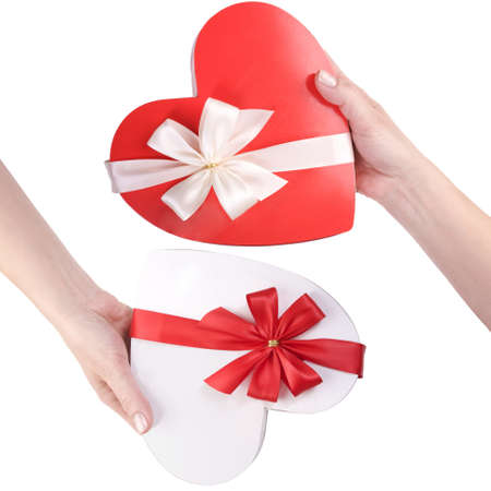 female hand holding red and white gift boxes in heart shape with a bow isolated on white background  photo