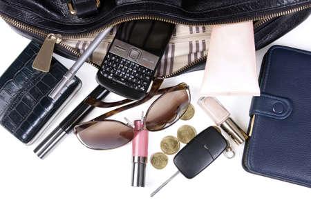 woman handle success: Content of Womens handbag on white