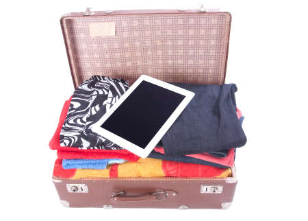 Vintage leather suitcase overstuffed with Tablet gadget over white photo