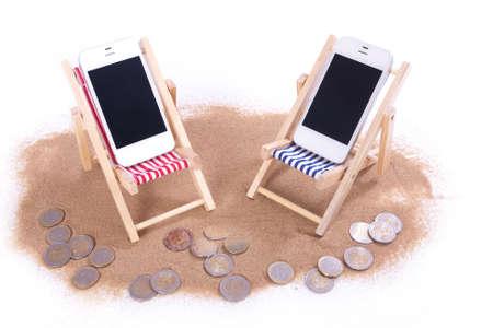 흰색 위에 모래에 장난감 해변의 자에 두 개의 휴대 전화