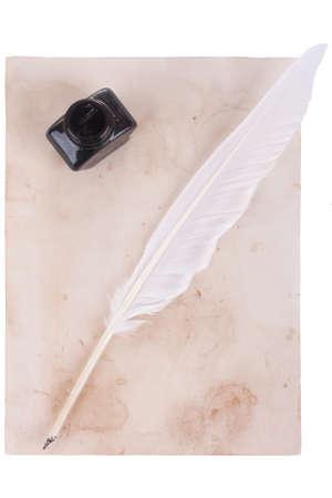 pluma de escribir antigua: La pluma blanca Botella de pluma y tinta sobre fondo de papel viejo Foto de archivo