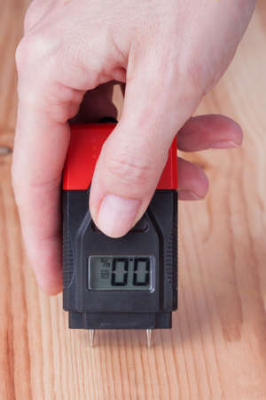 Female hand measuring moisture in wooden wall 스톡 콘텐츠