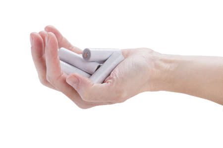 armful: female hand kept in an armful batteries over white Stock Photo