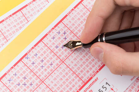 lottery win: male hand filling fountain pen lotto ticket Stock Photo