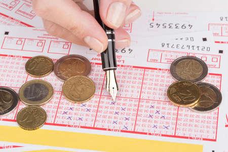 lotto: female hand filling fountain pen lotto ticket Stock Photo