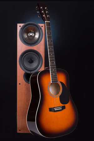 acoustic systems: high loudspeaker tower with acoustic guitar over black background Stock Photo