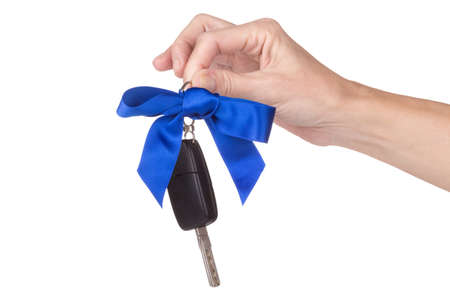 finger bow: female hand holding car keys with bow over white