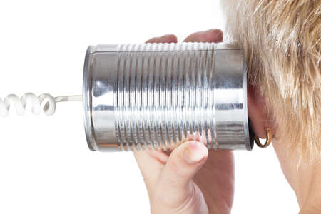 tin can phone: female hand holding a tin can phone to his ear over white