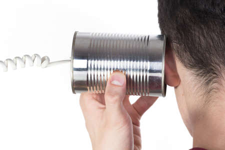 tin can phone: Male hand holding a tin can phone to his ear over white Stock Photo
