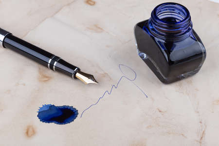 blots: fountain pen lying on old paper with blots and inkwell