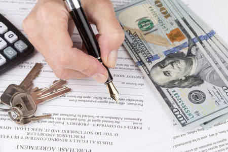 dollaro: mano femminile riempie un accordo per l'acquisto di appartamenti