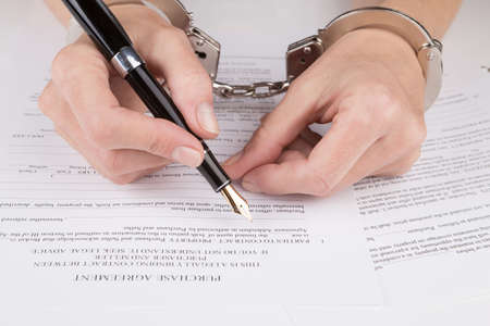 purchase: Female hands in handcuffs fill the contract on purchase Stock Photo