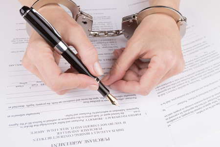 handcuffs female: Female hands in handcuffs fill the contract on purchase Stock Photo