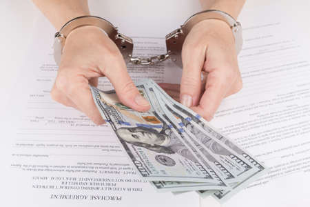 handcuffs female: Female hands in handcuffs hold dollars over the purchase contract Stock Photo