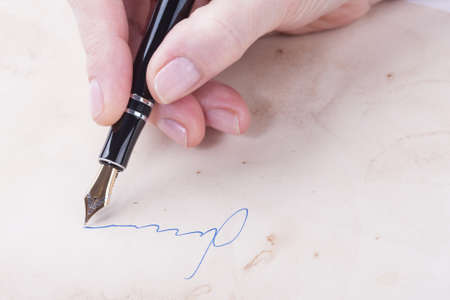 testament schreiben: A female hand signs of the old fountain pen
