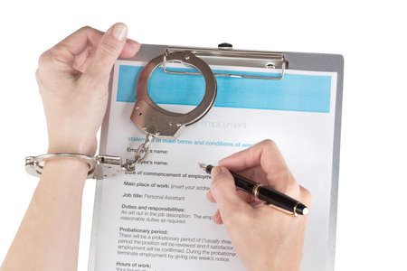handcuffs female: female hands in handcuffs signs the employment contract over white