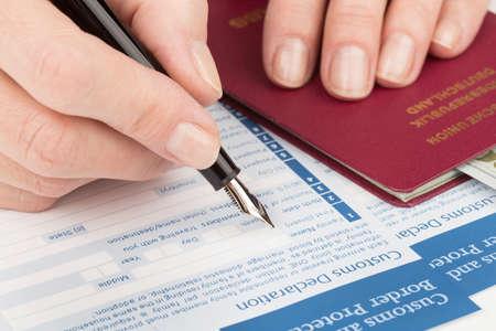 declaration: female hand  fills customs declaration german travel passport