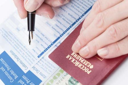 declaration: female hand  fills customs declaration russian travel passport