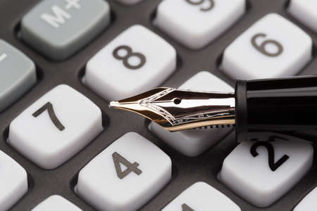 paycheck: Fountain pen lying on calculator