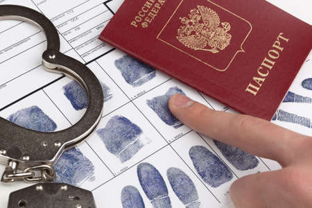 Fingerprint card with russian travel passport and handcuffs Stock Photo