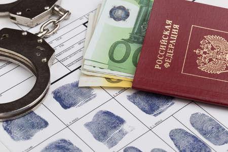 fingerprinting: Fingerprint card with russian travel passport and handcuffs Stock Photo