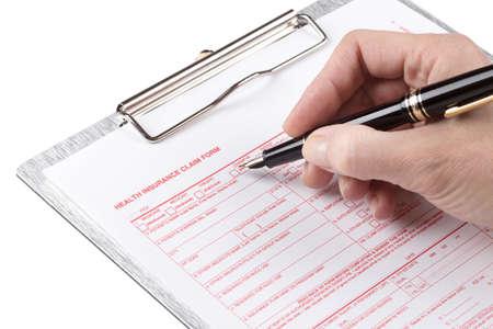 fills: female hand fills health insurance claim form