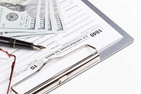 income tax: Income Tax Return Form with fountain pen and dollars