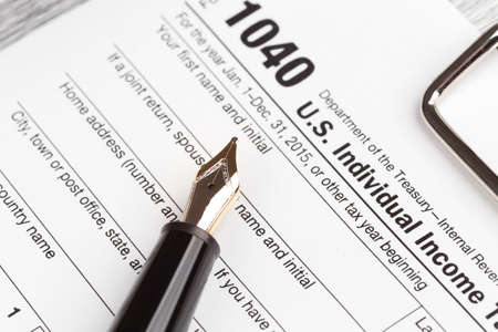 filing document: Income Tax Return Form with fountain pen
