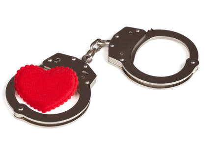 cuffed: heart in handcuffs on the white background