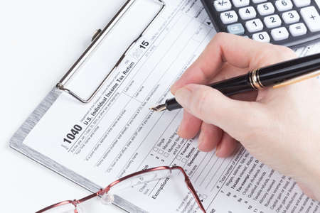 filling out: female hand filling out Income Tax Return Form