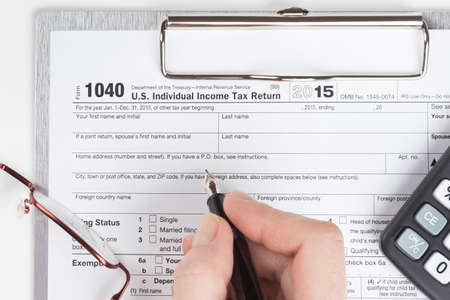 income tax: female hand filling out Income Tax Return Form
