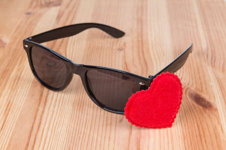wayfarer: sunglasses wayfarer with heart symbol over wooden background