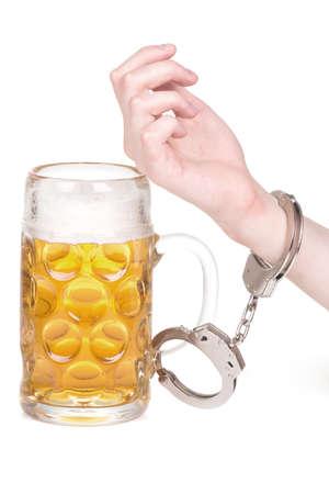 cuffed: hand handcuffed to a beer mug over white Stock Photo