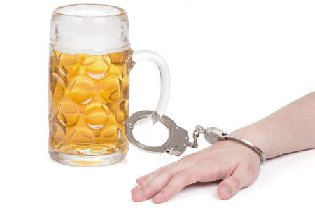 hand cuff: hand handcuffed to a beer mug over white Stock Photo