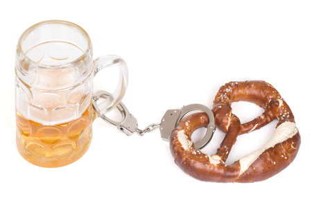 chained: pretzel chained with handcuffs to beer mug over white