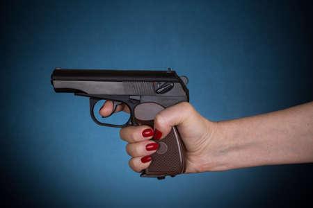female hand holding gun over dark blue background