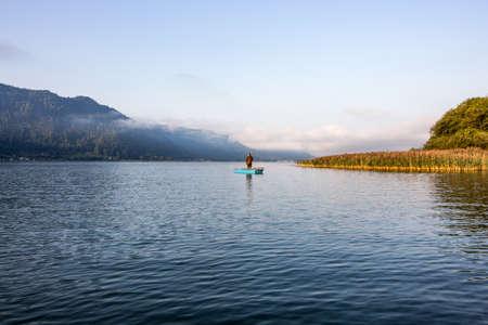 oneself: Fisherman on a lake at dawn Stock Photo