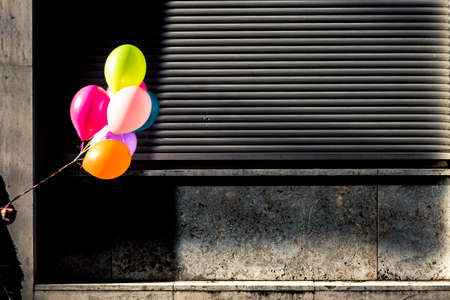 Colorful helium balloons in front of shutters Stock Photo