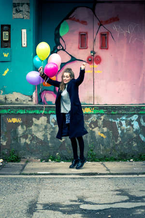 girl holding balloons at abandoned industrial area Stock Photo