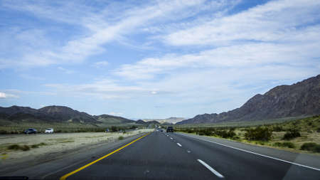 driving on an open road with hills in the far in nevada/california