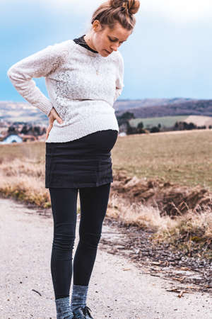 young pregnant woman outdoors in rural landscape Zdjęcie Seryjne
