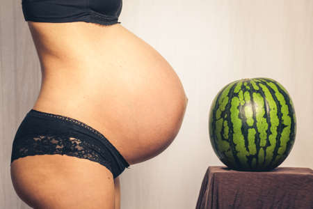 huge pregnant belly compared to a watermelon