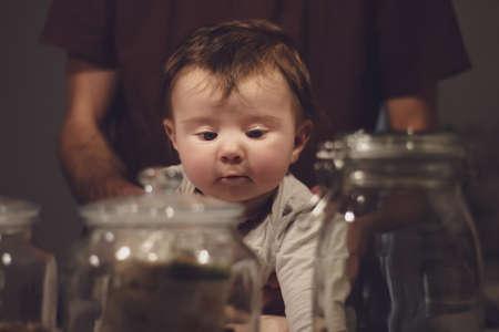 baby sitting on kitchen worktop with jars Stock Photo
