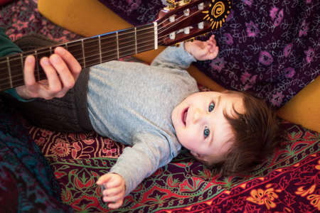 Baby is making music with a guitar at home Banco de Imagens